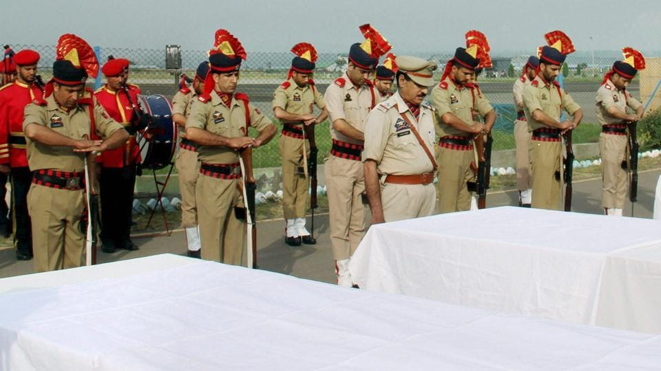 Police personnel pay tributes to the Amarnath Yatris who were killed by militants, at an airport in Srinagar on July 11.