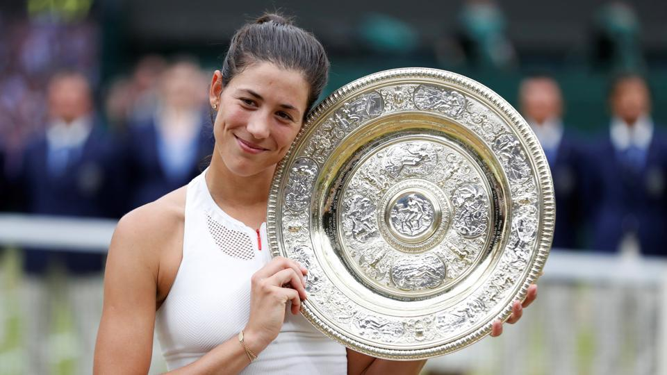 Spain's Garbine Muguruza poses with the trophy as she celebrates winning the Wimbledon women's singles final against Venus Williams on Saturday. Catch highlights of the Wimbledon women's singles final between Garbine Muguruza and Venus Williams here.