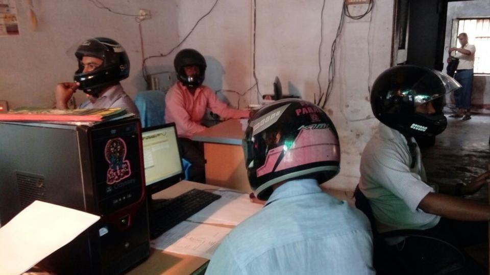 Pekerja Pejabat Kerajaan di India Bekerja Sambil Pakai Topi Keledar