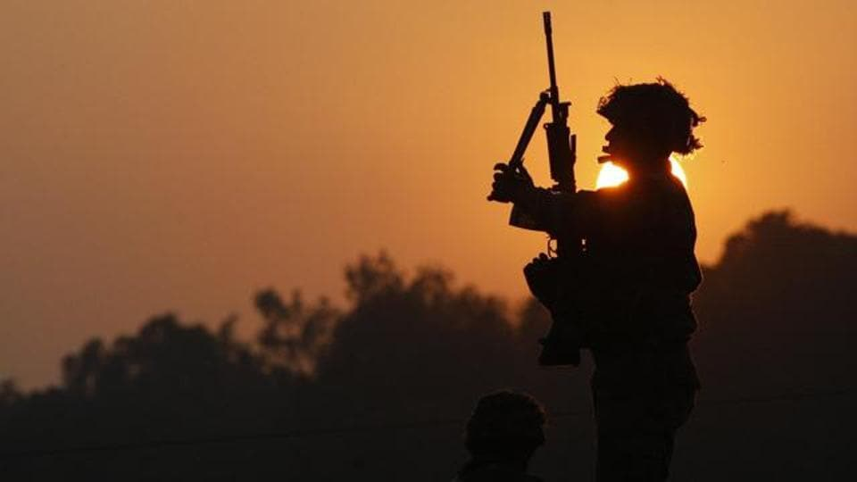 An Indian army soldier is silhouetted against the setting sun as he stands guard next to his colleague, outside the Indian air force base in Pathankot, India.