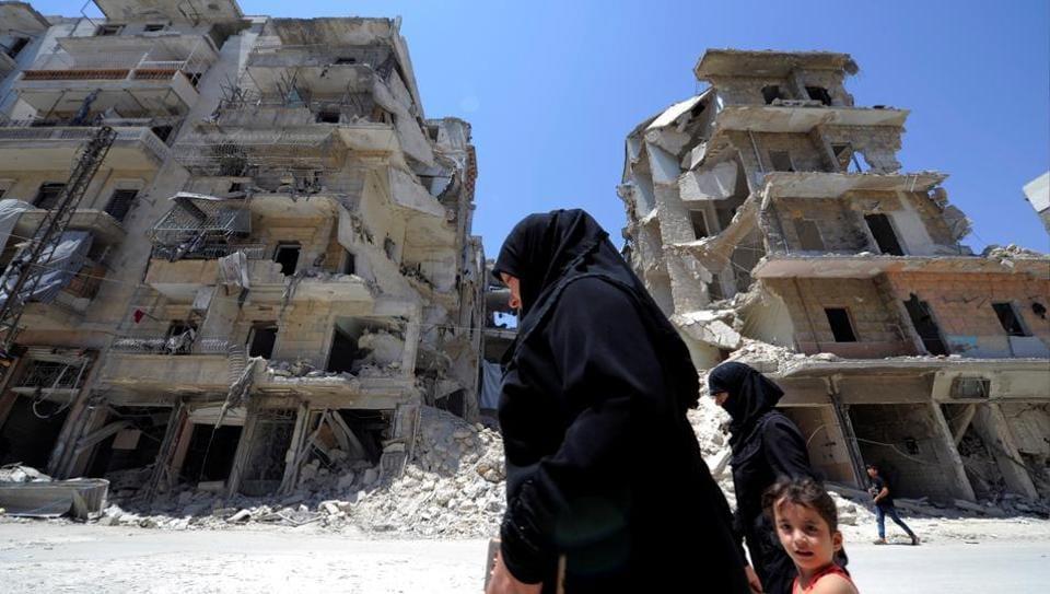 A woman walks with a child past damaged buildings at Bustan al-Qasr neighbourhood in Aleppo, Syria.
