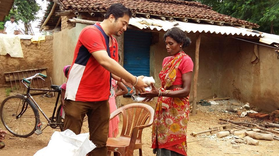 A young philanthropist - Mangesh Jha distributing sanitary napkin among villager during his menstrual health campaign at Jonha village in Ranchi