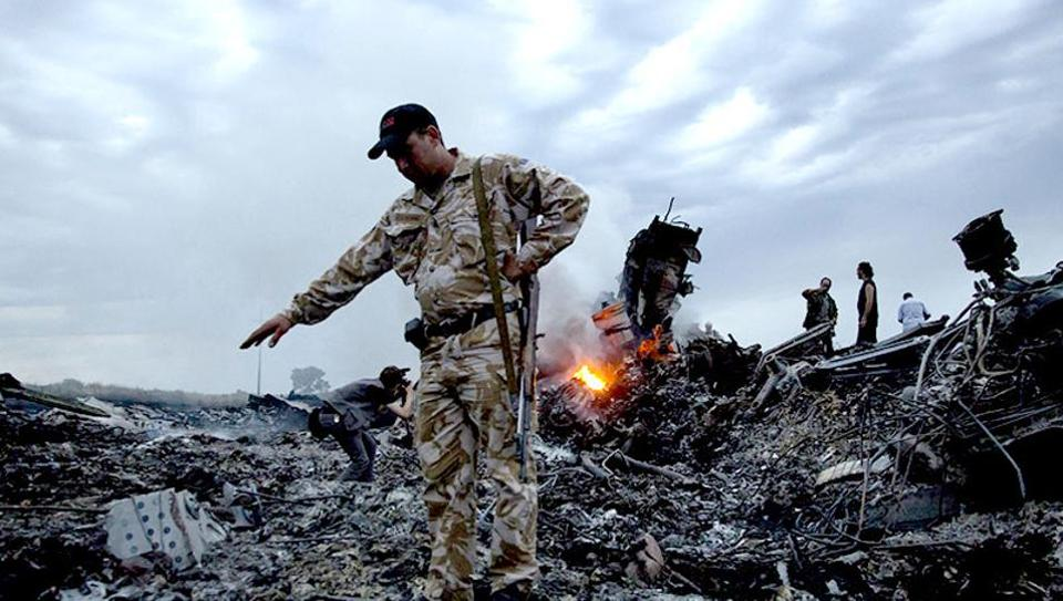 A file photo of people walking on the debris at the crash site of the Malaysia Airlines Flight MH17 Ukraine.