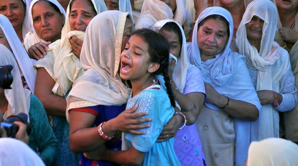Kajal (C), daughter of slain Indian soldier Lance Naik Ranjeet Singh, wails as the mortal remains of her father are brought to her home in Burn village, about 28km from Jammu. (AFP)