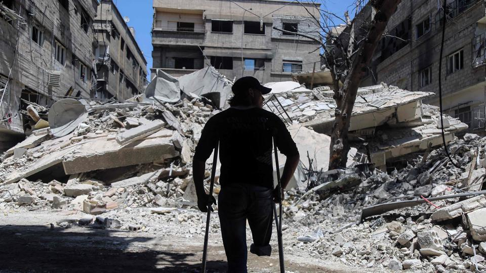 A Syrian amputee uses crutches to walk next to a building that was destroyed following a reported air strike on the rebel-held town of Ayn Tarma, in Syria's eastern Ghouta area (AMER ALMOHIBANY/AFP)