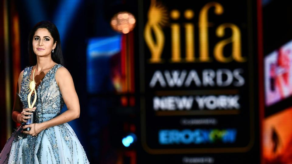 Katrina Kaif holds a trophy on stage.