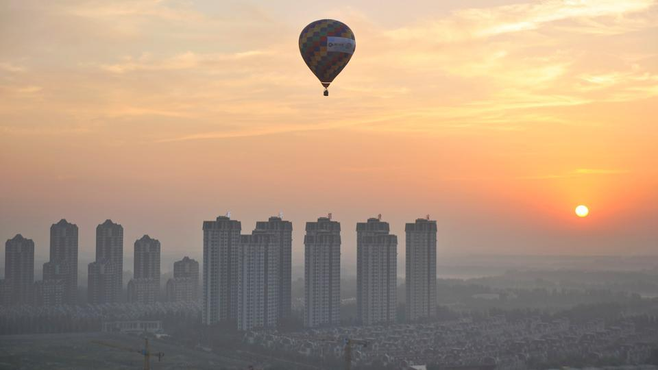 A hot air balloon flies over residential buildings in Wuqing District of Tianjin, China.  (REUTERS)