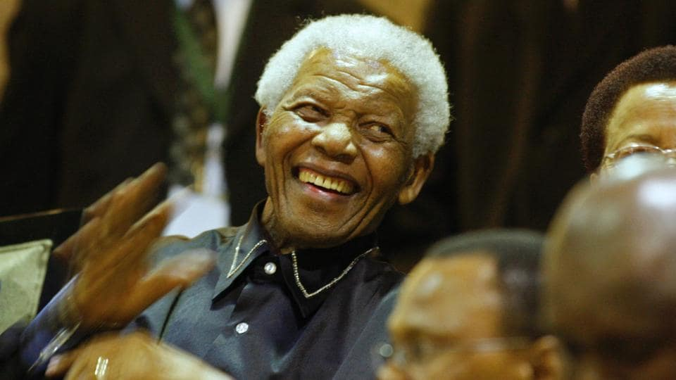 This file photo taken on February 11, 2010, shows former South African president Nelson Mandela (L) as he laughs while sitting beside his wife Graca Machel (R) in the parliament gallery in Cape Town.