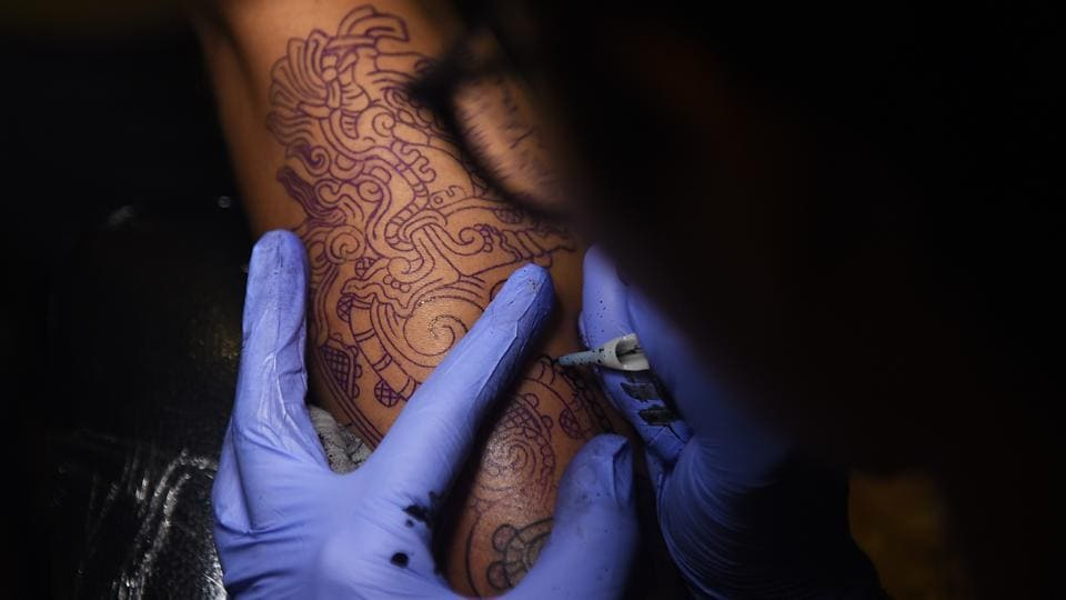 A tattoo artist fills in an intricate design at a workshop in Dadar. (Satyabrata Tripathy/HT Photo)