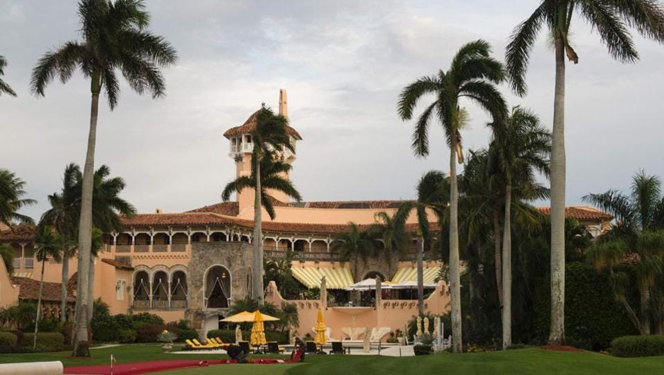 This photo taken on December 30, 2016 shows workers as they lay out the red carpet at Mar-a-Lago Club in Palm Beach, Florida.