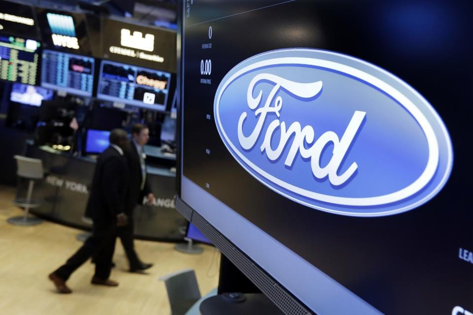 The logo for the Ford Motor Company appears above a post on the floor of the New York Stock Exchange.