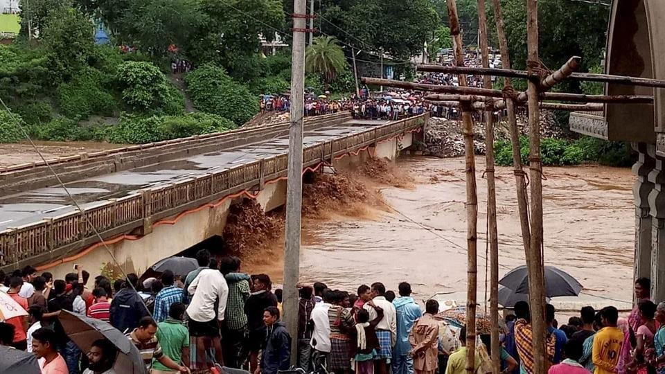 People gather near the swollen Nagabali river after flash floods, in Rayagada. Railway services have been badly hit due to heavy rain causing flood like situation in Odisha.  (PTI)