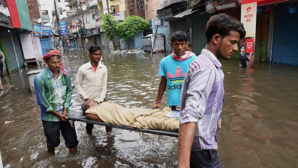 People shift a patient to a safer place from a flooded locality after heavy downpour, in Patna, Bihar.  Heavy rainfall has brought life to a standstill, causing  landslides and floods in many parts of the country. Floods in  northeastern states have killed at least 83 people and displaced more than a million. There has been serious flooding in Bihar, Assam, Gujarat, Arunachal Pradesh and parts of Maharashtra.  (PTI)