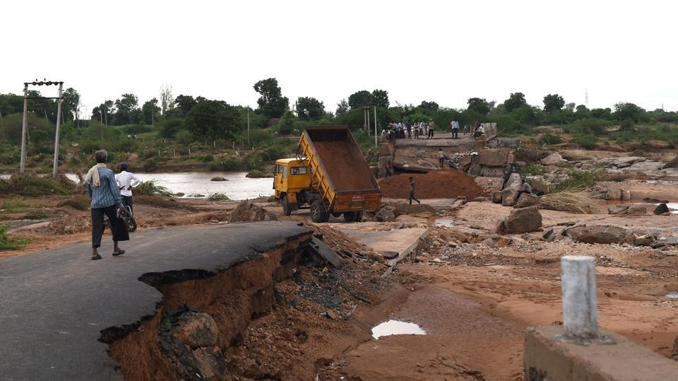 Indian labourers use heavy machinery to repair a flood damaged bridge over the River Bhogavo in the village of Aya in Surendranagar District, some 150kms from Ahmedabad. Heavy monsoon flooding has killed four people and alteast sicx others missing in the state of Gujarat, officials said on Sunday. (AFP)