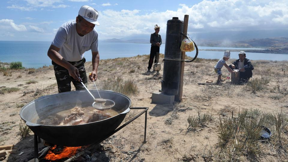 A Kyrgyz man cooks traditional meals on an open fire. Samples of nomadic Kyrgyz cuisine such as Besh Barmak (lamb with noodles) , Boorsok  and Ak Serke (Nomad's soup) were presented as dietary samples of life in the steppes. (Vyacheslav Oseledko / AFP)