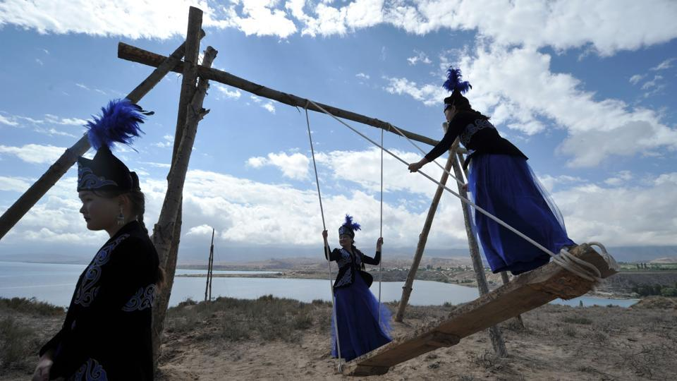 Kyrgyz women wearing traditional clothes enjoy a ride on a swing during the 'Ethno Fest' festival. (Vyacheslav Oseledko / AFP)