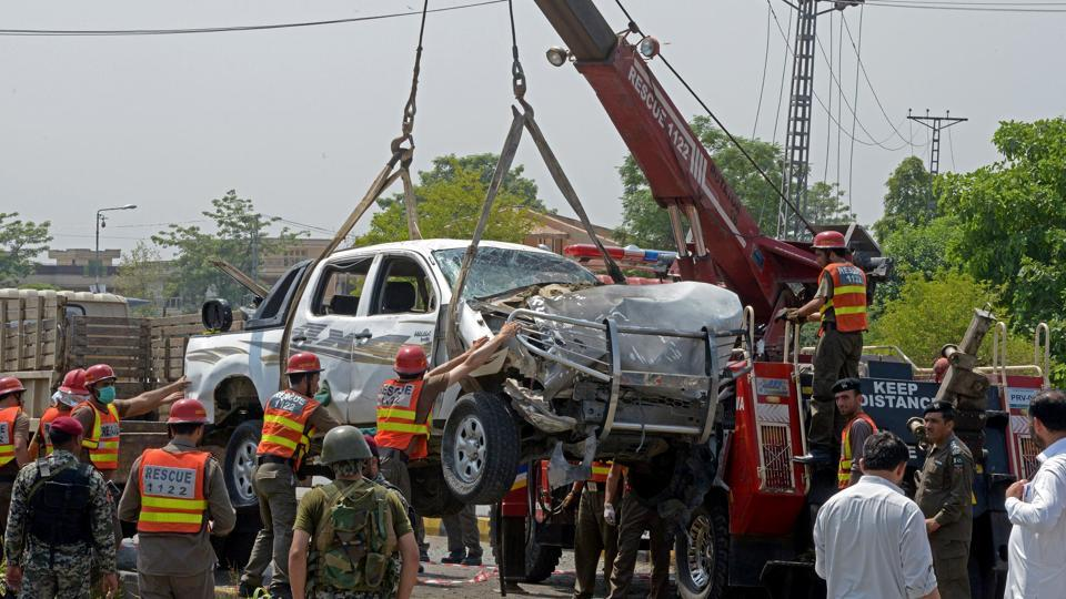 Pakistani officials use a crane to lift a security vehicle at the site of suicide bomb attack in Peshawar on July 17, 2017. A suicide bomber struck a vehicle carrying members of the paramilitary Frontier Corps, killing two and wounding six more in an attack claimed by the Taliban.