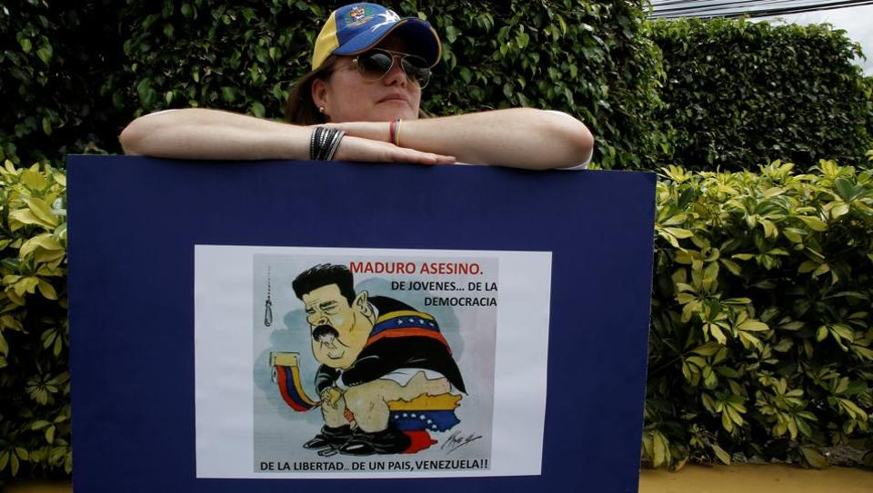 A woman holds a sign during an unofficial plebiscite against Venezuela President Nicolas Maduro's government, in San Jose, Costa Rica. Government opponents sought to deal a symbolic blow  to Venezuelan President Nicolas Maduro, casting votes in an unofficial referendum designed to reject his controversial plan for a constitutional overhaul. More than 7.1 million people voted in a symbolic rejection of President Nicolas Maduro's plan to rewrite the constitution. (Juan Carlos Ulate / REUTER)