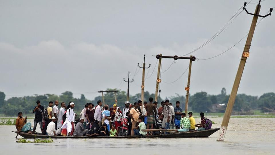 Villagers use a boat to cross a flooded road at Asigarh village in Morigaon district . Assam is the worst hit with 53 lives lost so far in floods and landslides with some 2 million people displaced. The overflowing Brahmaputra River has also completely marooned the Kaziranga wildlife sanctuary in Assam, forcing animals to flee to safer areas. (Anuwar Hazarika / REUTERS)