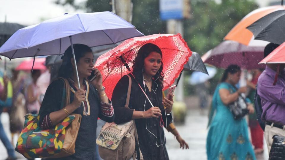 Officegoers in Vashi brave the rain to make it to work. (Satyabrata Tripathi/ht photo)