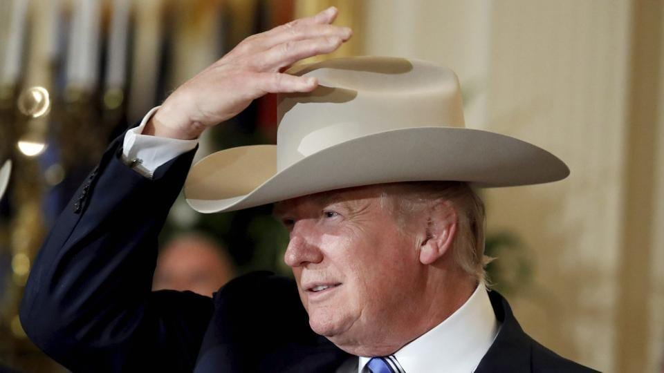 President Donald Trump tries on a Stetson hat during a