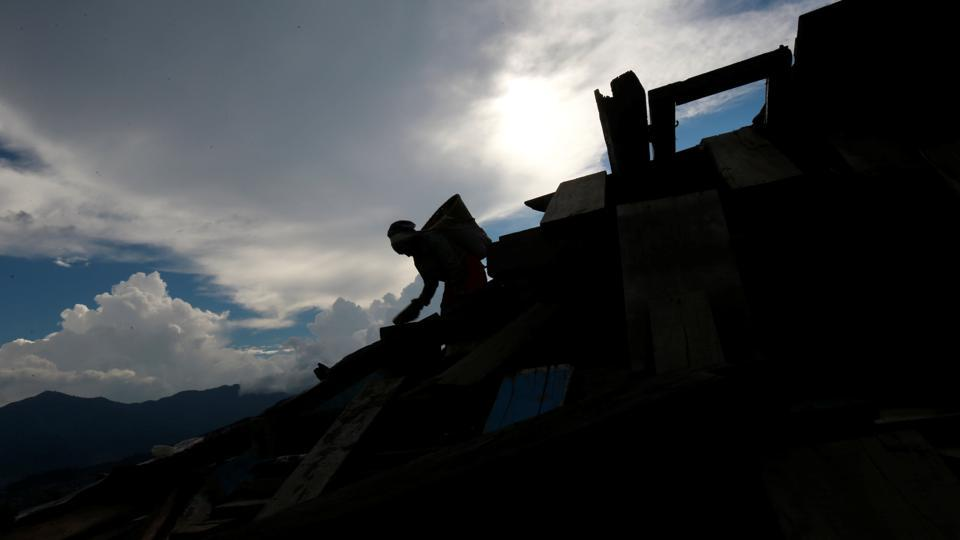 A woman is silhouetted as she carries bricks from the debris of a monastery damaged during the 2015 earthquake, in Swayambhunath Stupa, in Kathmandu, Nepal.