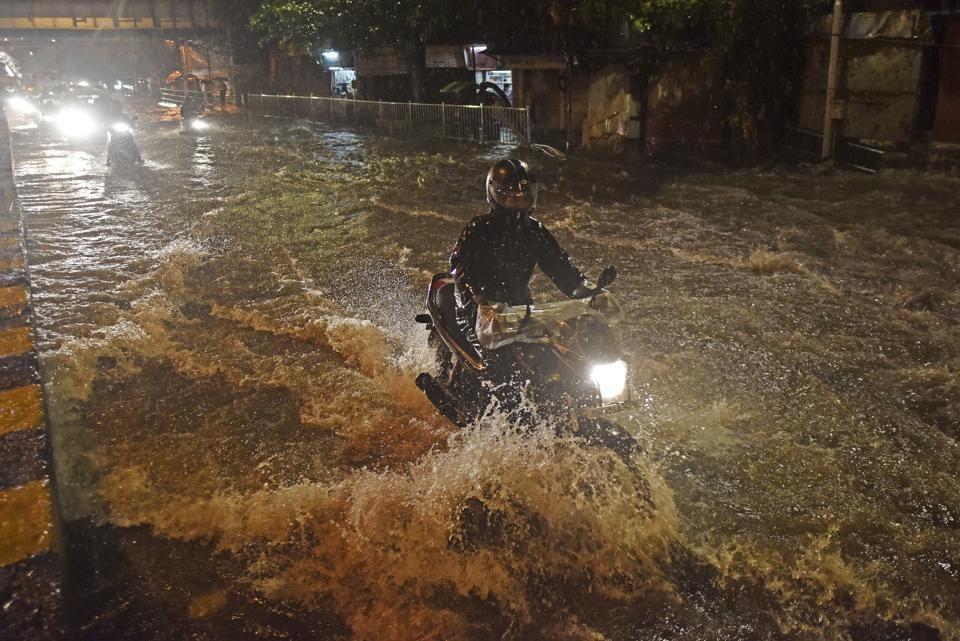 A biker tries to make his way through a waterlogged street at Kings Circle on Monday.