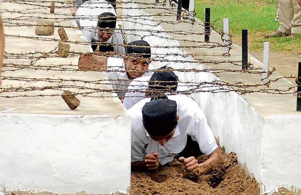 Cadets crawling under barbed wires during teh training session.  (Bharat Bhushan/HT)