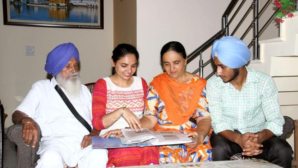 Family members of Harmanpreet including (from left) Grandfather, Sister Hemjeet Kaur, Mother Satvinder Kaur and brother cherishing memories by looking at an album at her home in Moga on Friday (HT PHOTO )