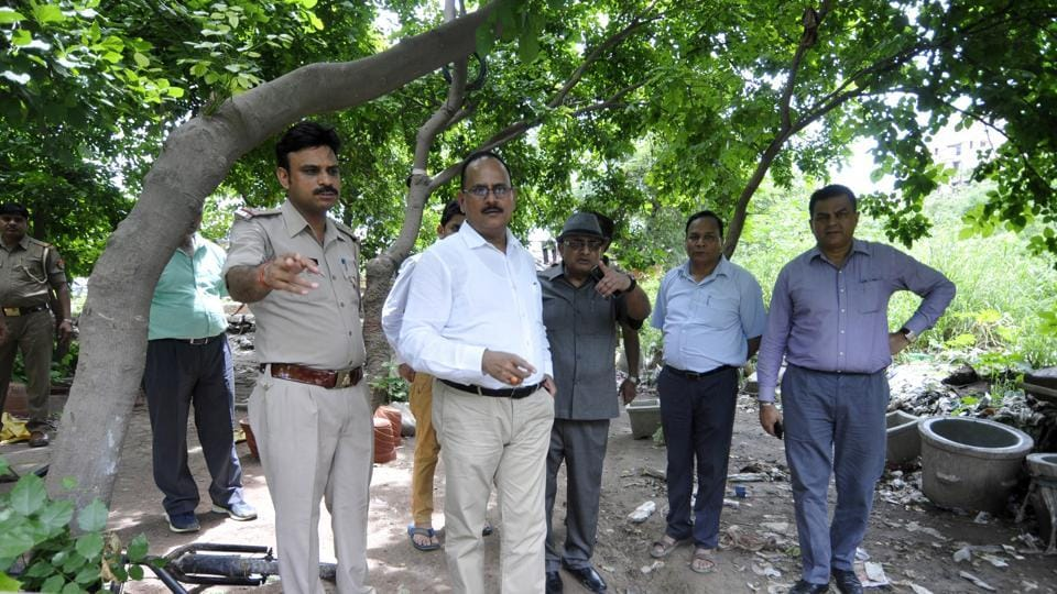 Noida additional CEO Rakesh Kumar Mishra (in white shirt), chief engineer Hom Singh (in grey)reached the spot on Friday when machines found it difficult to proceed due to encroachments.