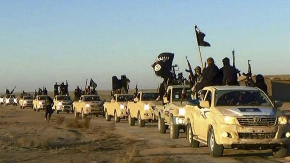 Militants of the Islamic State group hold up their weapons and wave its flags on their vehicles in a convoy on a road leading to Iraq, in Raqqa, Syria.