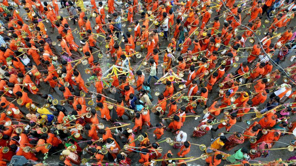 Karwariyas make their pilgrimage carrying the kawar (containers of holy water balanced on the sides of a pole) on their shoulders during the month of Sawan in Jabalpur. (PTI)