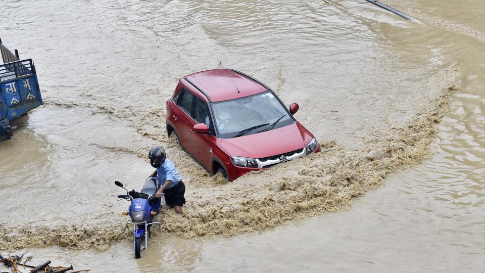 Commuters wade through logged water after heavy rain on NH 24, in East Delhi. (Ajay Aggarwal / HT Photo)