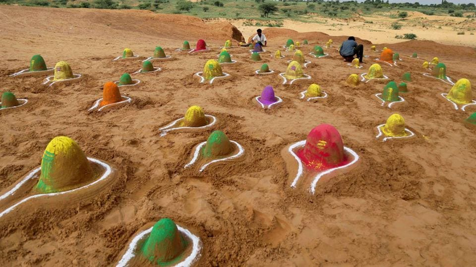 A sand artist creates 'Shivlings', idols symbolic of Lord Shiva in Pushkar, Rajasthan. (PTI)