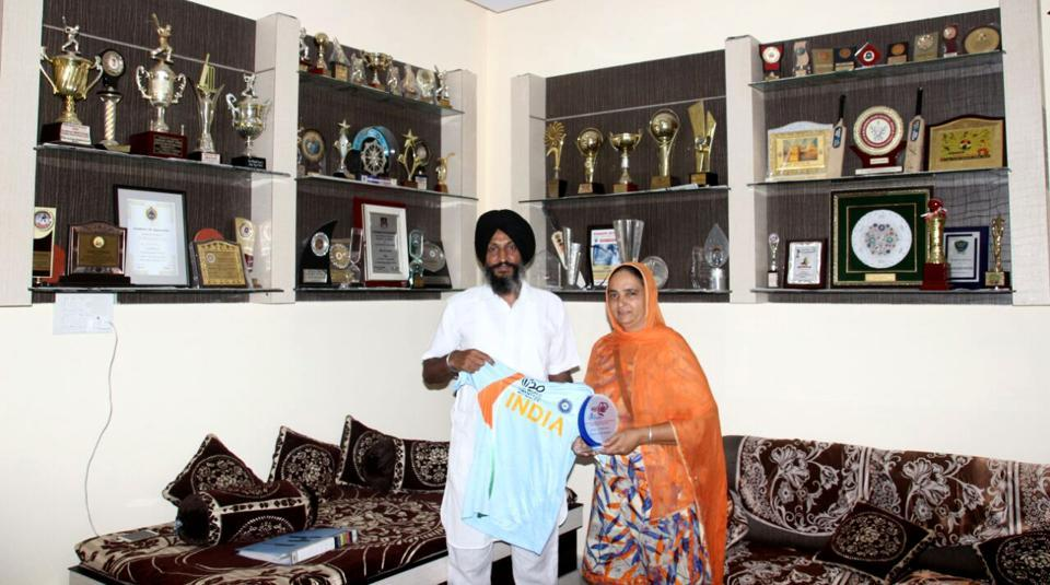 Harmanpreet's father Harmandar Singh and mother Satvinder Kaur showing a T-shirt and awards won by her.  (HT Photo )