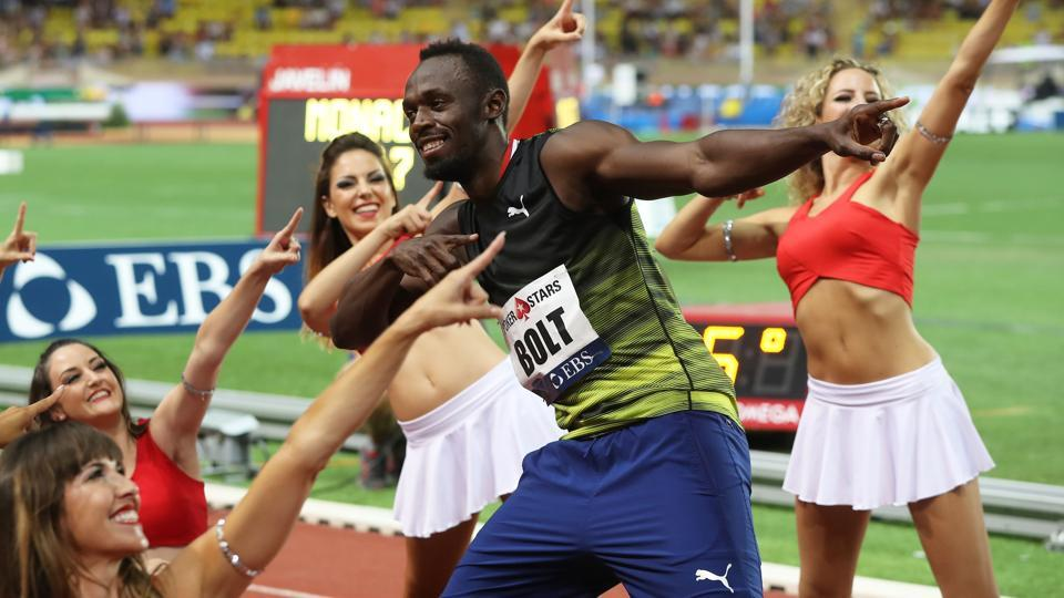 Jamaica's Usain Bolt (C) dances with pom-pom girls as he celebrates winning the men's 100m event at the IAAF Diamond League athletics meeting in Monaco on Friday.