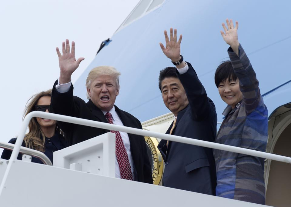 US President Donald Trump and Japanese Prime Minister Shinzo Abe, accompanied by their wives first lady Melania Trump and Akie Abe, before boarding Air Force One at Andrews Air Force Base on February 10, 2017.