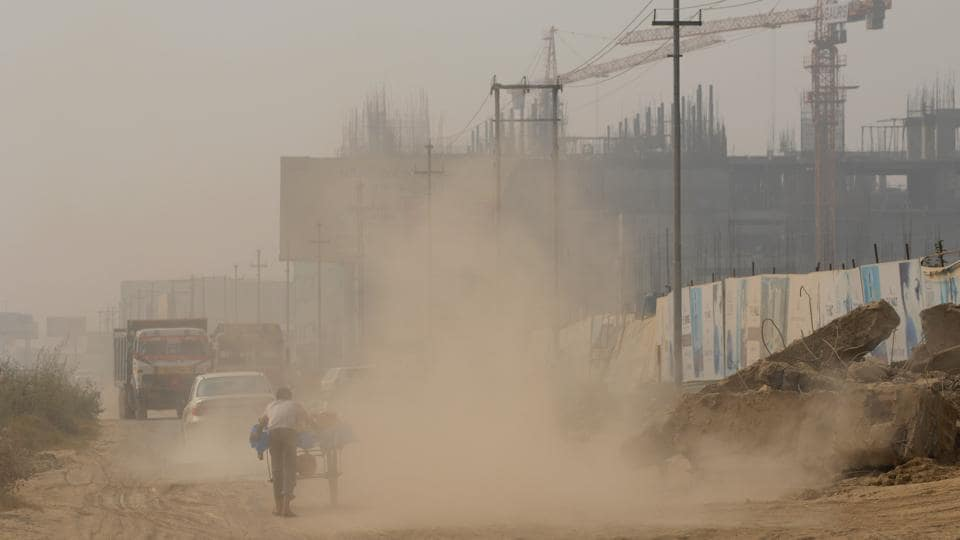 Trucks loaded with construction material kick up dust, adding to an already polluted air in Noida in December 2016.