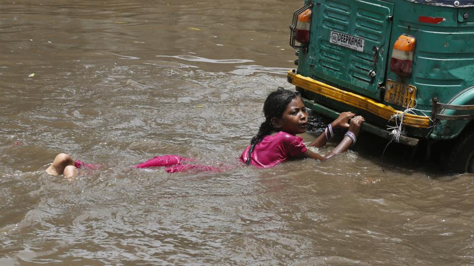 A girl holds on to the back of an auto-rickshaw as she plays in a flooded street with other children after a heavy monsoon rain in Ahmadabad, Gujarat. (Ajit Solanki / AP)
