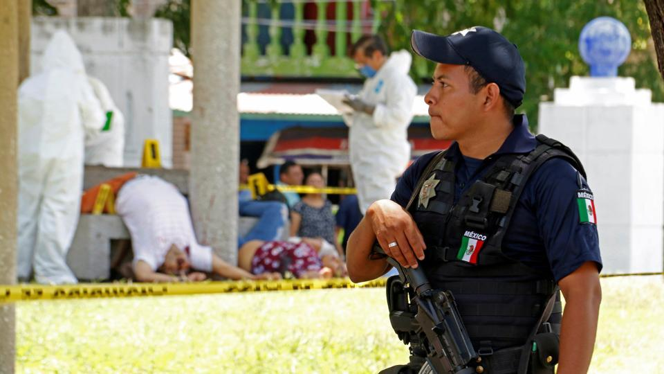 A policeman keeps watch as forensic technicians work at a crime scene where unknown assailants gunned down four persons at a park in Villahermosa, Mexico, July 21, 2017.