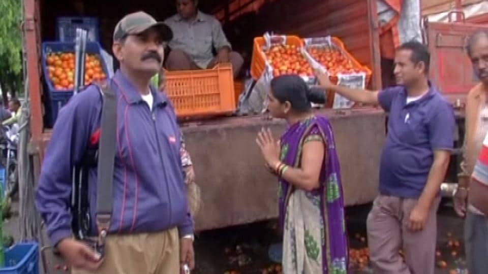 An armed guard stands by a tomato truck at the Indore vegetable market .