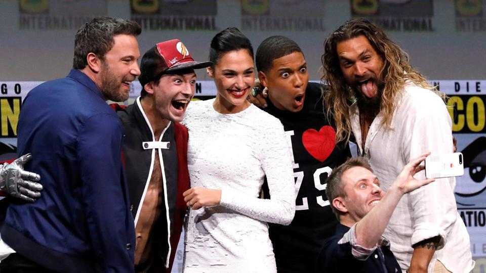 Ben Affleck, Ezra Miller, Gal Gadot, Ray Fisher and Jason Momoa pose with moderator Chris Hardwick at Comic-Con.