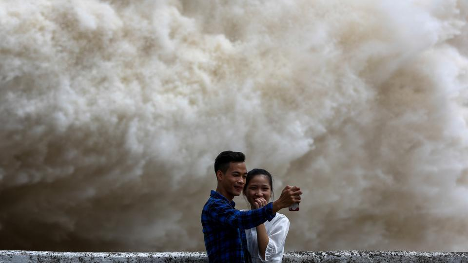 A couple takes a selfie as Hoa Binh hydroelectric power plant opens the flood gates after a heavy rainfall caused by Talas typhoon in Hoa Binh province, outside Hanoi, Vietnam. (Kham / REUTERS)