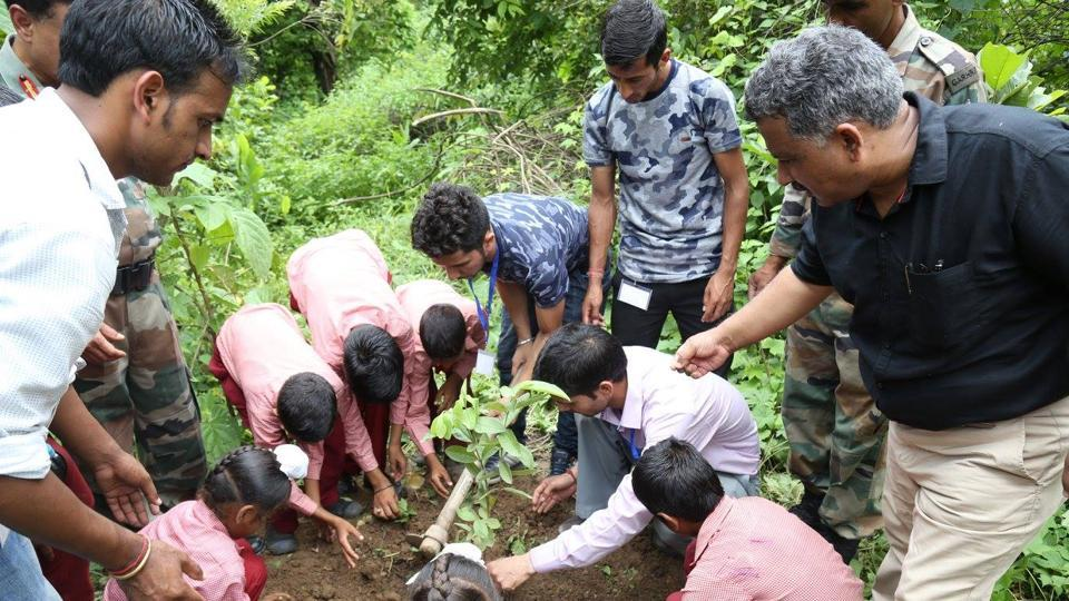 School students plant a sapling in the Army Cantonment area in Dehradun.