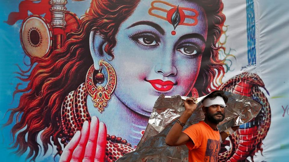 A Kanwaria or devotee of Hindu god Shiva shelters from the rain in front of a poster of Lord Shiva in New Delhi, India. (Cathal McNaughton / REUTERS)