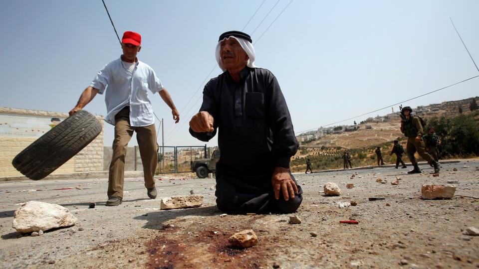 A Palestinian man gestures at the scene where a Palestinian who attempted to stab Israeli soldiers was shot dead by Israeli troops in the West Bank village of Tuqu near Bethlehem. (Mussa Qawasma  / REUTERS)