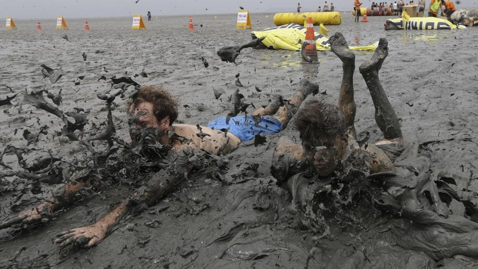 Men slide in the mud during the Boryeong Mud Festival at Daecheon Beach in Boryeong, South Korea. Started in 1998, the Boryeong Mud Festival was first put on as a PR stunt after a range of cosmetics was launched using mud from the Boryeong mud flats. The annual festival is famous for attracting the largest numbers of foreign visitors among local festivals. (Ahn Young-joon / AP)