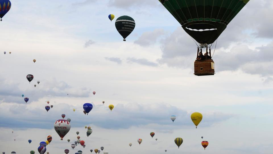 Hot-air balloons fly over Chambley-Bussieres airbase, northeastern France, during the international hot air balloons meeting 'Mondial Air Ballons' in Hageville. (JEAN-CHRISTOPHE VERHAEGEN / AFP)