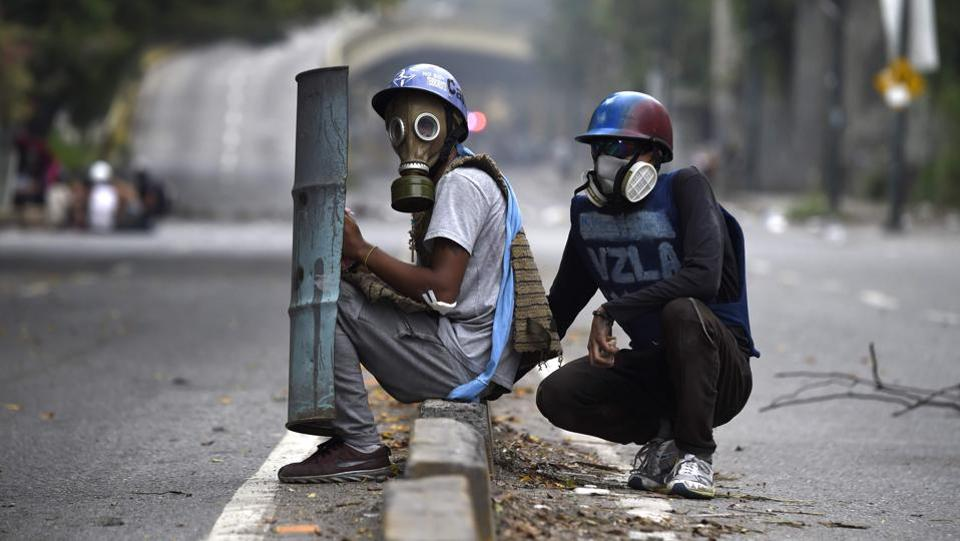 Opposition demonstrators clash with riot police during an anti-government protest in Caracas. A 24-hour nationwide strike got underway in Venezuela Thursday, in a bid by the opposition to increase pressure on beleaguered leftist President Nicolas Maduro following four months of deadly street demonstrations. (JUAN BARRETO / AFP)