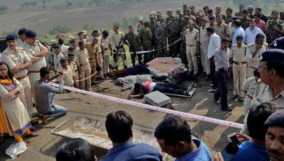 Police officers and Special Task Force soldiers stand beside bodies of the eight suspected SIMI operatives who escaped the high security jail in Bhopal on October 31, 2016. The men were killed in an encounter at the Acharpura village on the outskirts of Bhopal.